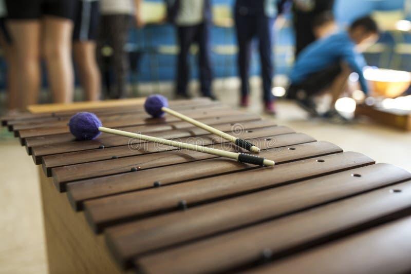Xylofoon en trommelstokken in een muziekklasse met kinderen stock afbeelding