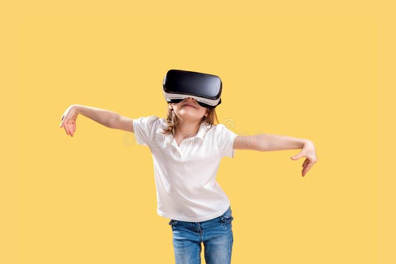 ??7 y 在黄色背景在正式成套装备的o佩带VR玻璃投入在兴奋实施隔绝的 ?? 免版税图库摄影