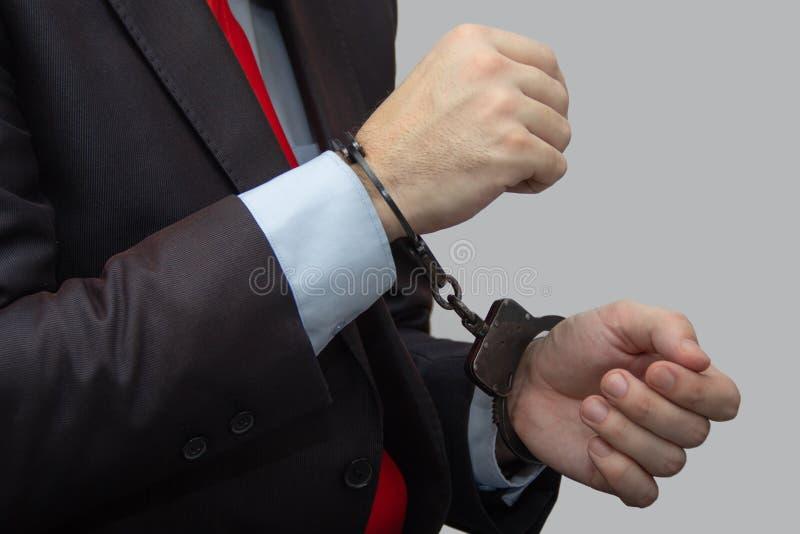 Y detuvo a las personas sospechosas en esposas, hombre de negocios en la policía imagenes de archivo
