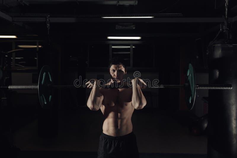 - Y - el ejercicio limpio del tirón - hombre joven que hace entrenamiento del levantamiento de pesas en el gimnasio imagen de archivo libre de regalías