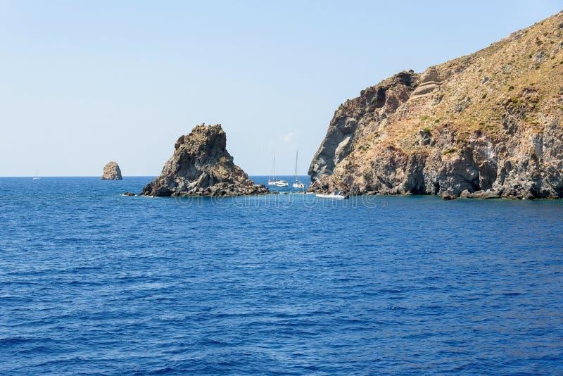 Yacht alla costa rocciosa dell'isola di Lipari fotografia stock