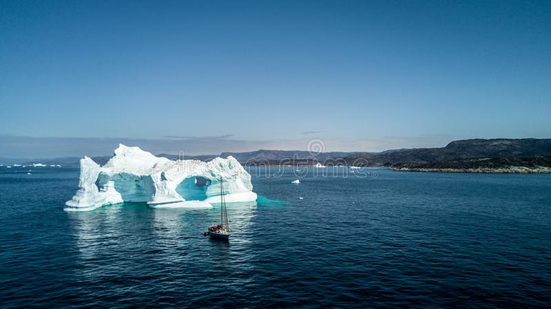 Yacht and amazing iceberg. Greenland view from drone. stock image
