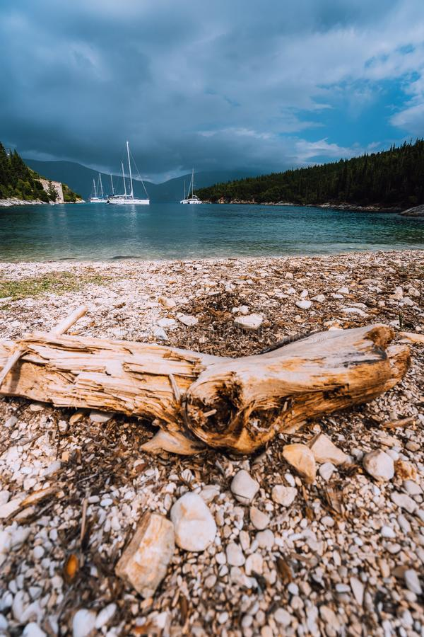 Yacht anchoring in the deep harbour. Dramatic storm cloudscape. Overcast, rainy day.  stock photo