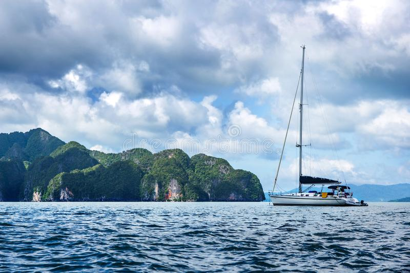 Yacht on the background of small mountains. Big clouds are not the sky, beautiful scenery stock images