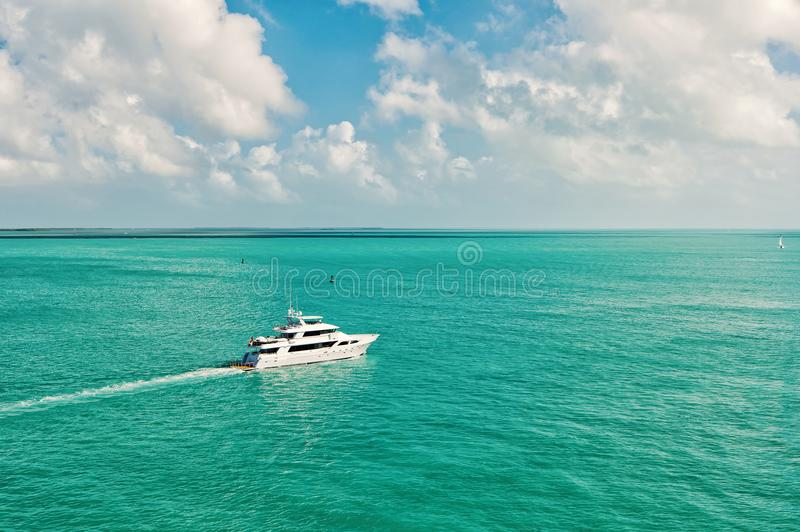 Yacht or boat floating on turquoise water sunny summer outdoor. Cruise touristic boat or yacht floating on turquoise water and blue cloudy sky on natural royalty free stock photo