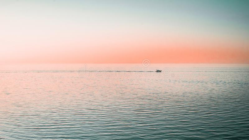 A yacht on the calm waters of the Gulf of Trieste. A singular yacht on the calm waters of the Gulf of Trieste taking in the setting sun and the pink sky royalty free stock image