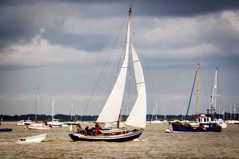 Yacht che traversa il fiume sotto la vela fotografia stock