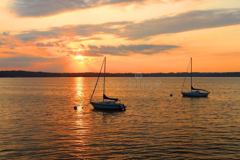 Yacht che vanno alla deriva sul lago durante il bello tramonto di estate fotografia stock