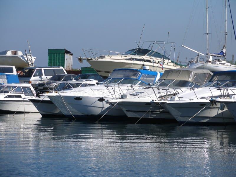 Yacht-club. Moored yachts, sea port, white boats, yacht-club, ships near quay, pier, jetty, coast, water mirror stock image