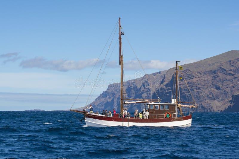 Yacht com os turistas perto de Los Gigantes que procura baleias e golfinhos, Tenerife, Ilhas Canárias, Espanha foto de stock