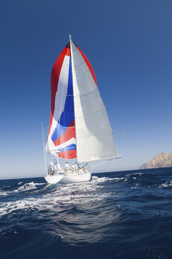 Yacht con la vela variopinta nell'oceano immagini stock