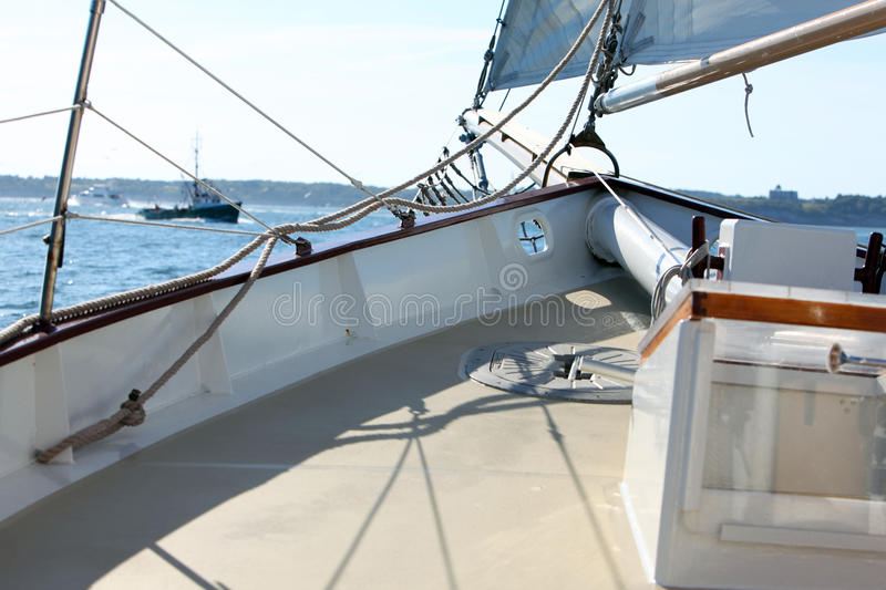 Yacht deck. Close-up of the deck of a yacht with fishing boat in background stock photo