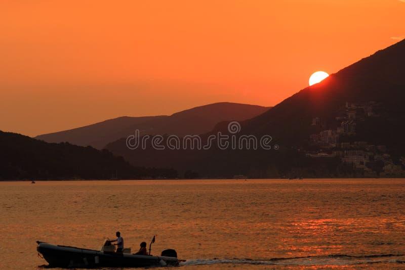 Yacht in den Strahlen der untergehenden Sonne gegen das Berg-backg lizenzfreies stockbild