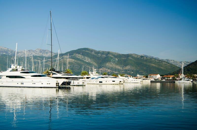 Yacht ed imbarcazioni a motore in porto adriatico su fondo delle montagne e del cielo blu fotografia stock