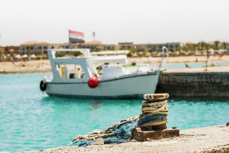 The yacht with the Egyptian flag docked at a pier in the Red Sea. On a sunny day,a mooring bollard on the pier royalty free stock images