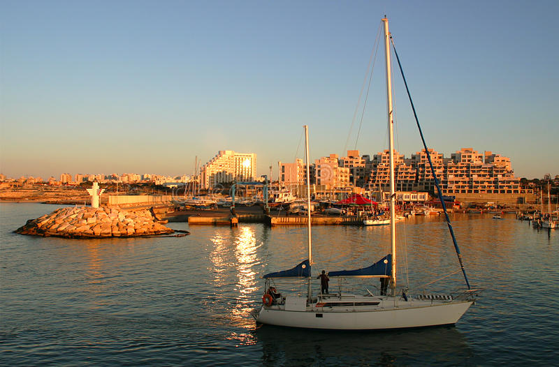 Yacht entering marina at sunset. royalty free stock photos