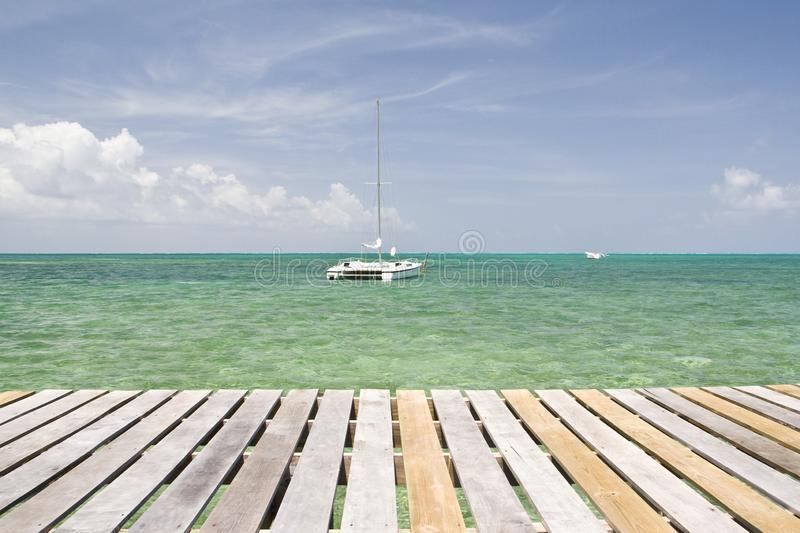 Yacht in front of wooden pier, Caye Caulker stock photo