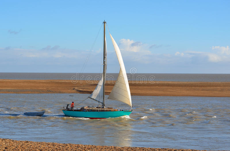 Yacht leaving Felixstowe Ferry at the mouth of the river Deben. royalty free stock image