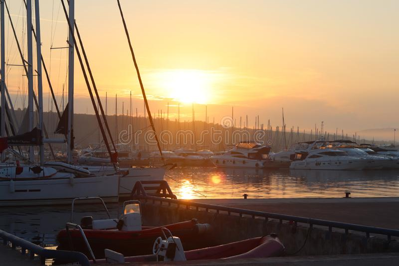 Yacht in the marina during the morning dawn sailing past the moored sailing yachts. Marine life style. Romantic and extreme rest o stock photography