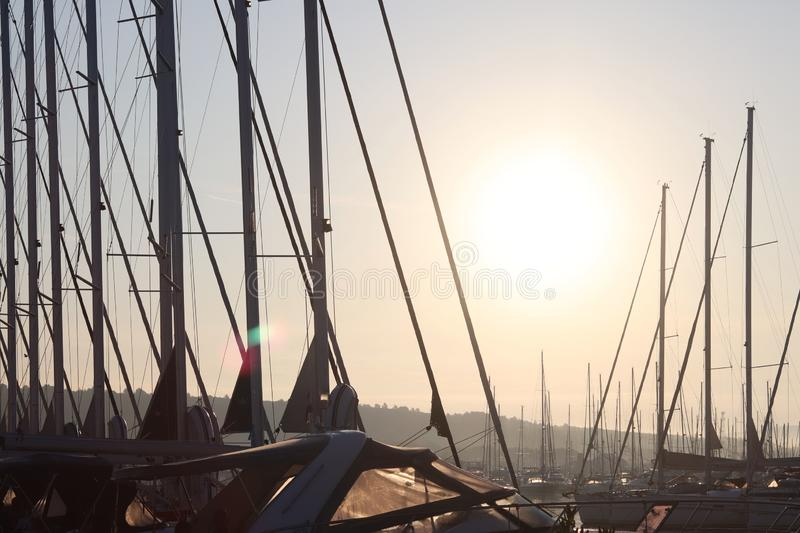 Yacht in the marina during the morning dawn sailing past the moored sailing yachts. Marine life style. Romantic and extreme rest o stock photo
