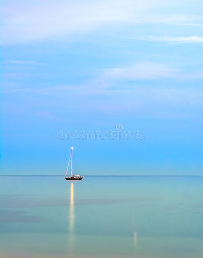 Yacht in the middle of sea. Yacht seaview light evening bluesky sunset bluewater horizon single sole desolate lonely fare away royalty free stock photo