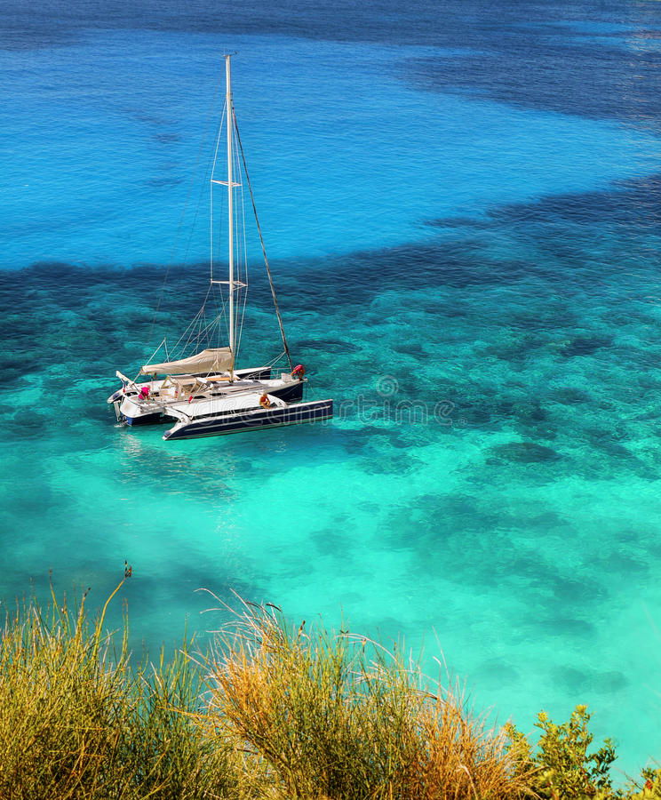 Yacht moored in tropical waters royalty free stock images