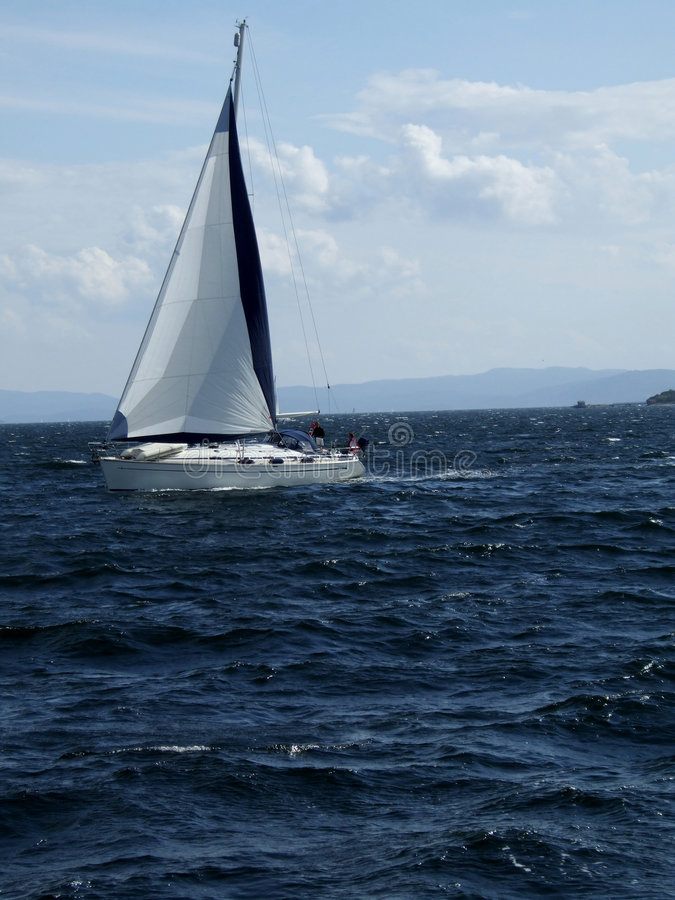 Yacht in ocean. A yacht gliding through the ocean. There's a cloudy blue sky in the background. Taken in Oslofjord, Norway royalty free stock photo