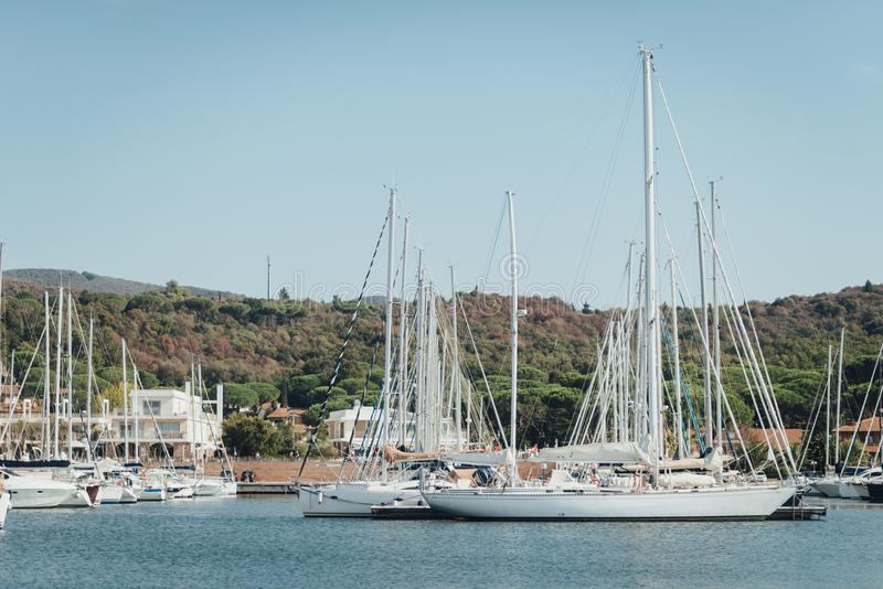 Yacht parking in harbor, harbor yacht club in Marina di Scarlino, Italy. Beautiful yachts on the background of the Italian coast royalty free stock image
