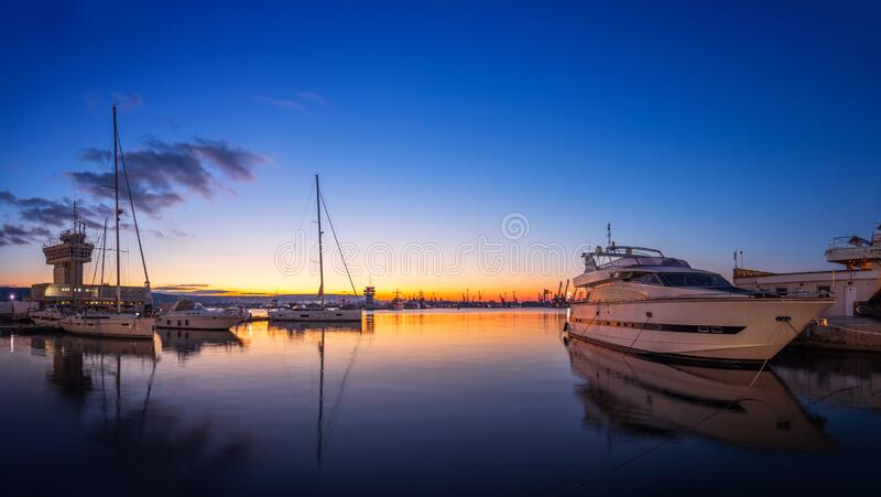 Yacht port and beautiful sunset over Varna, Bulgaria. Sailboat harbor, many beautiful moored sail yachts in the sea royalty free stock images