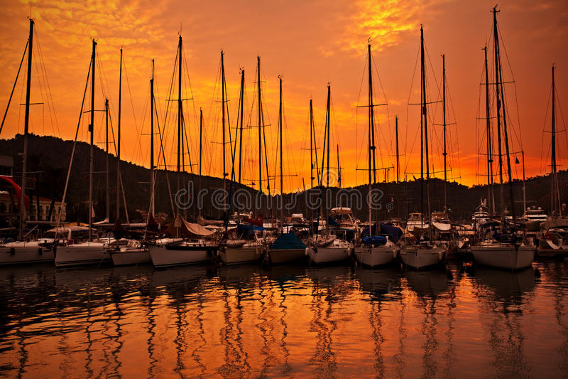 Yacht port over orange sunset. With row of luxury sailboats royalty free stock image