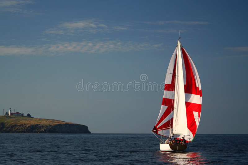 The Yacht with a red sail near island. stock image