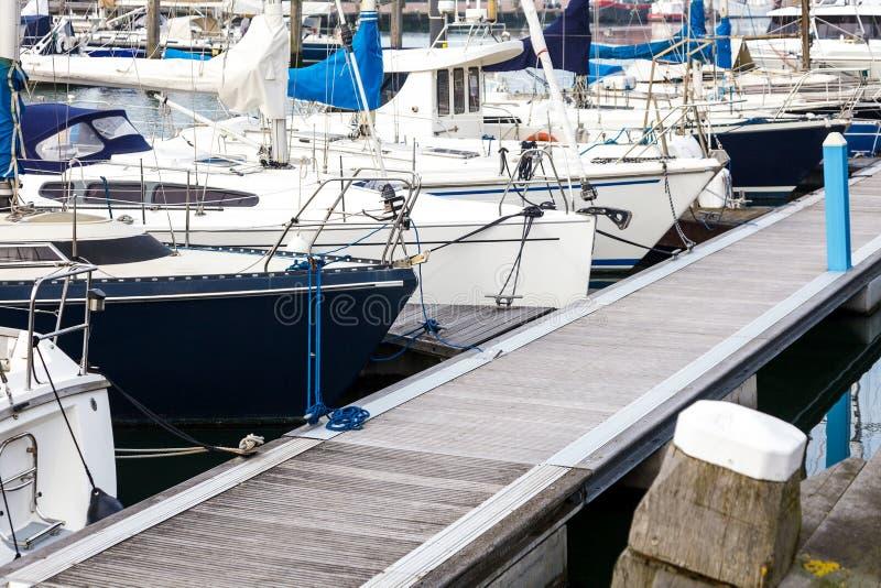 Yacht Reflexionssonnenlichtscheveningen-Höhle haag Holland des Norddockbootsseehafen-Himmelblau-Seehintergrundsonnenunterganghafe stockfoto