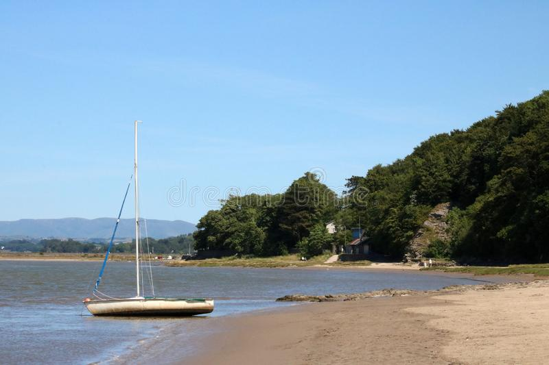 Yacht, River Kent estuary, Arnside, Cumbria. Yacht at edge of receding tide in River Kent estuary looking along the shoreline towards footpath to Arnside stock images