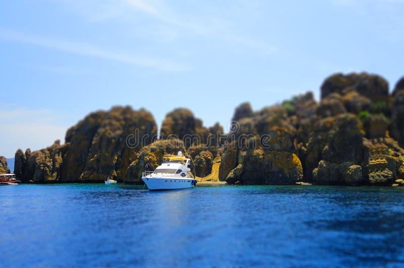 Yacht, rocks and blue sea, selective focus, effect tilt-shift stock photos