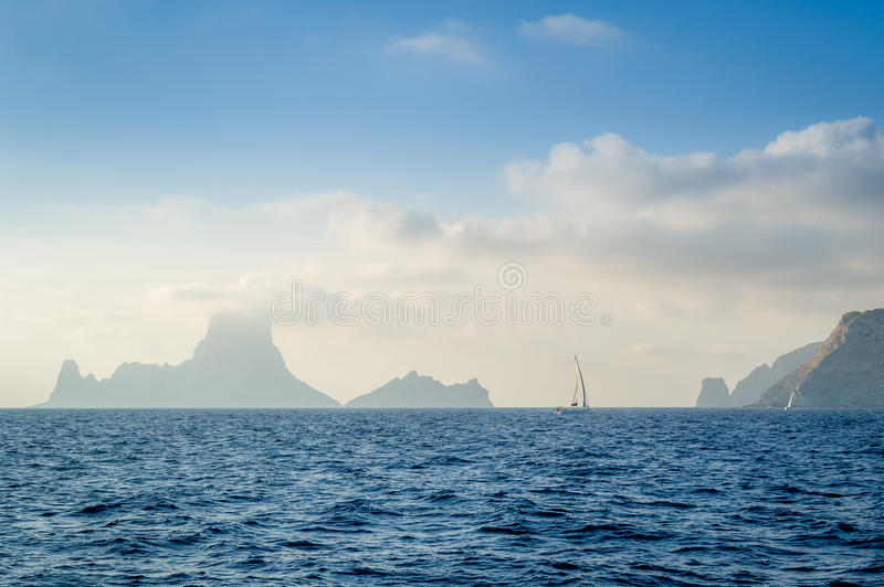 Yacht and rocks in the fog royalty free stock photography