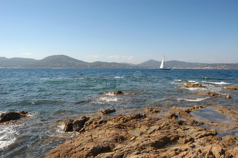 Yacht and rocks St Tropez. With St Maxime in the distance royalty free stock image
