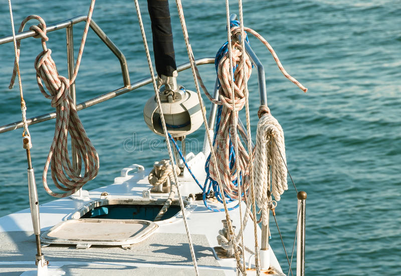 Marine ropes and knots. Marine ropes on white yacht at sea background. Details of a classic beautiful sailing yacht with ropes and knots on the deck royalty free stock image