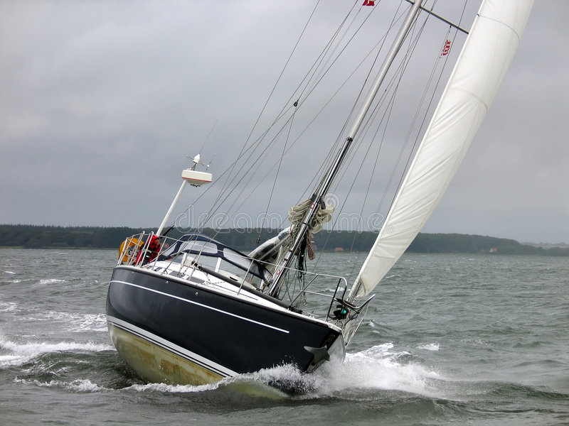 Yacht sailboat in a winter sail. Yacht racing in a windy dark winter day royalty free stock photos