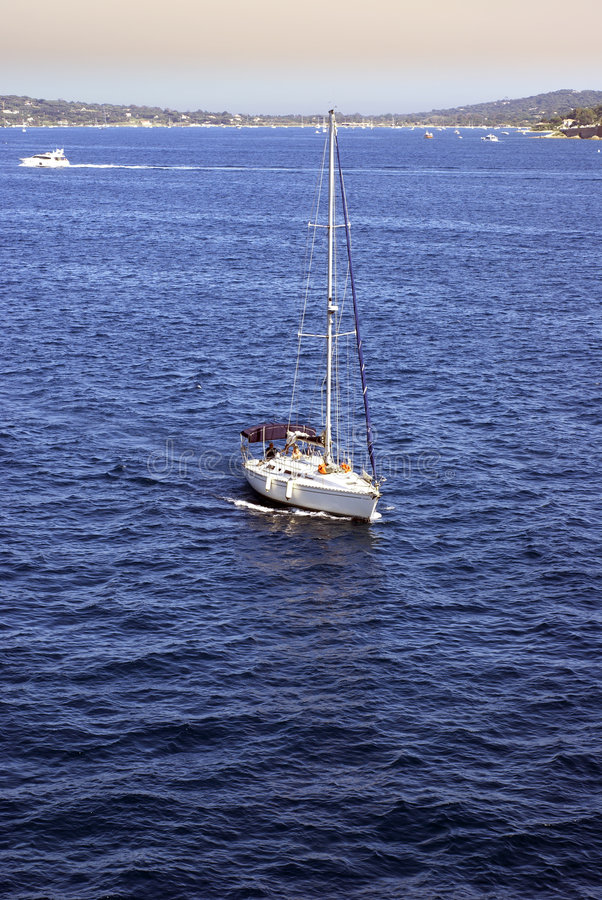 Yacht sailing in blue sea. High angle view of yacht sailing in blue sea with coastline in background royalty free stock images