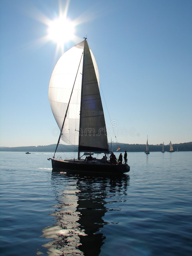 Yacht sailing on calm sea. With sun flare in background royalty free stock image