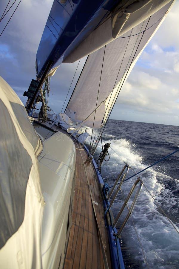 Yacht sailing in choppy sea stock photography