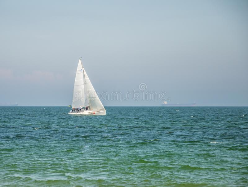 Yacht sailing near the coastline. The horizon line. Odessa City, Ukraine, May 2019, landscape, summer, beach, beautiful, blue, boat, color, concept royalty free stock photo