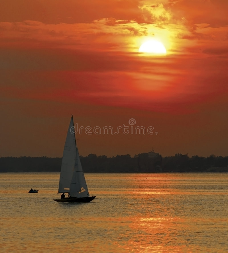 Yacht sailing in sunset royalty free stock images