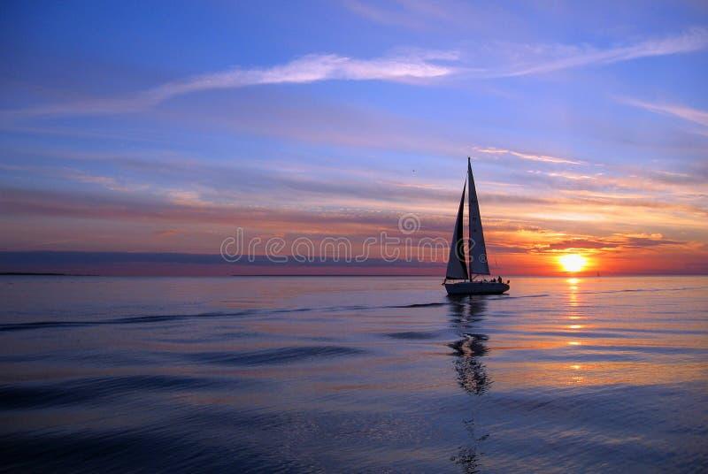 Yacht sailing at sunset stock photos