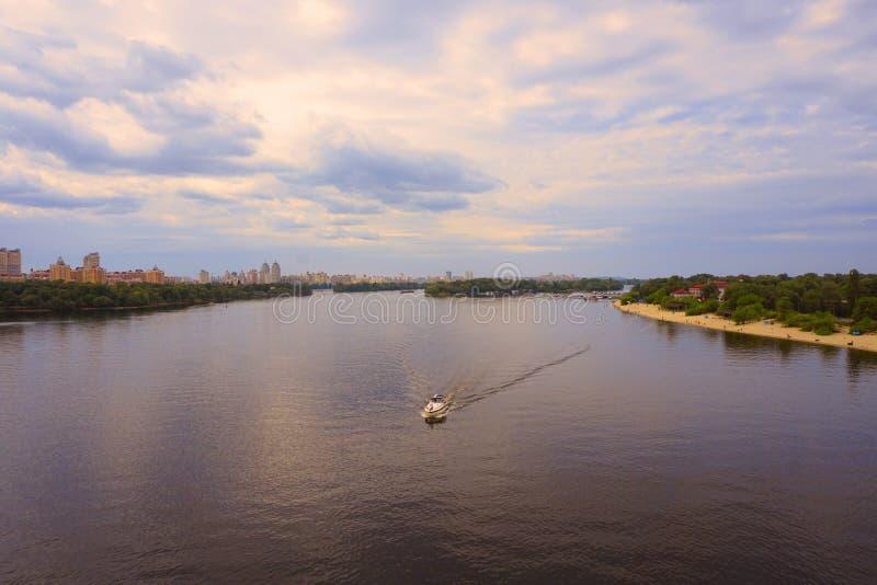 Yacht Schiff, Boot geht auf Oberfläche des Dnieper Dnipro, Dnepr-Fluss vor dem hintergrund der Stadtwolkenkratzer stockbild