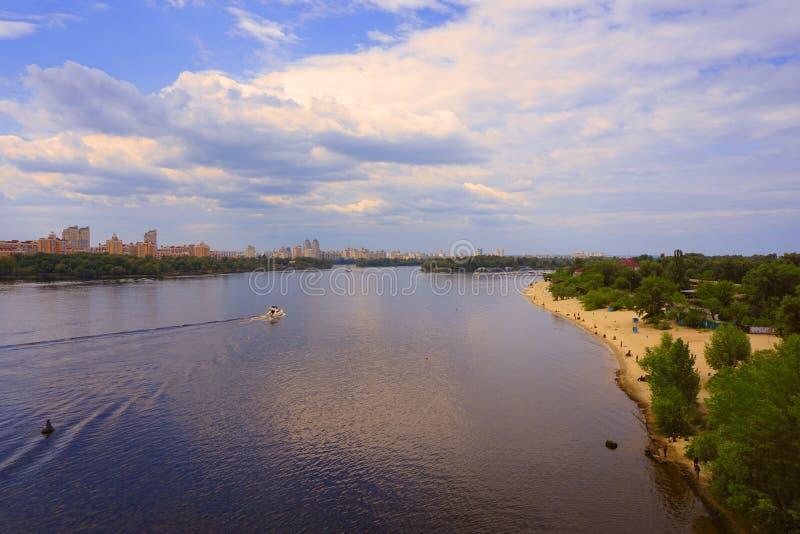 Yacht Schiff, Boot geht auf Oberfläche des Dnieper Dnipro, Dnepr-Fluss vor dem hintergrund der Stadtwolkenkratzer lizenzfreie stockbilder