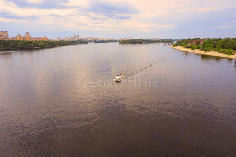 Yacht Schiff, Boot geht auf Oberfläche des Dnieper Dnipro, Dnepr-Fluss vor dem hintergrund der Stadtwolkenkratzer lizenzfreie stockfotos