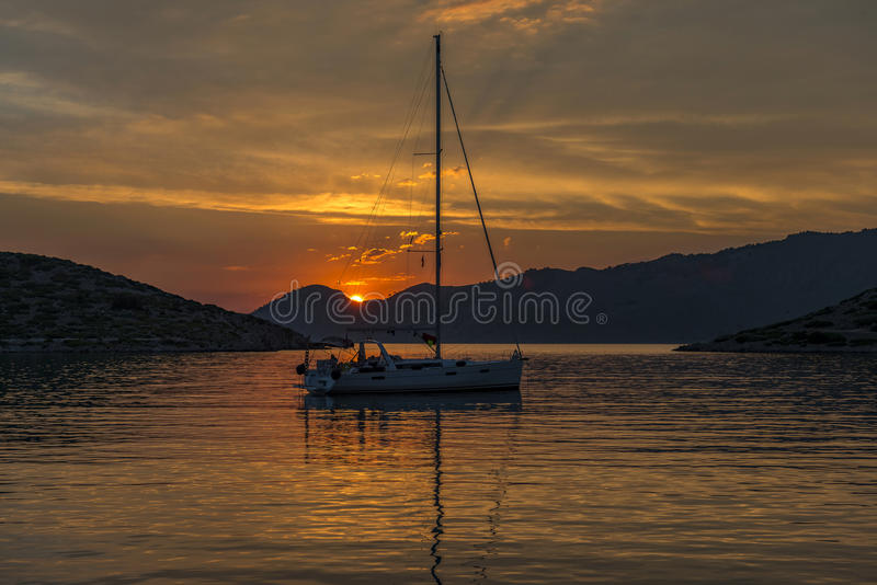 Yacht on sea and orange clouds at sunset royalty free stock photo