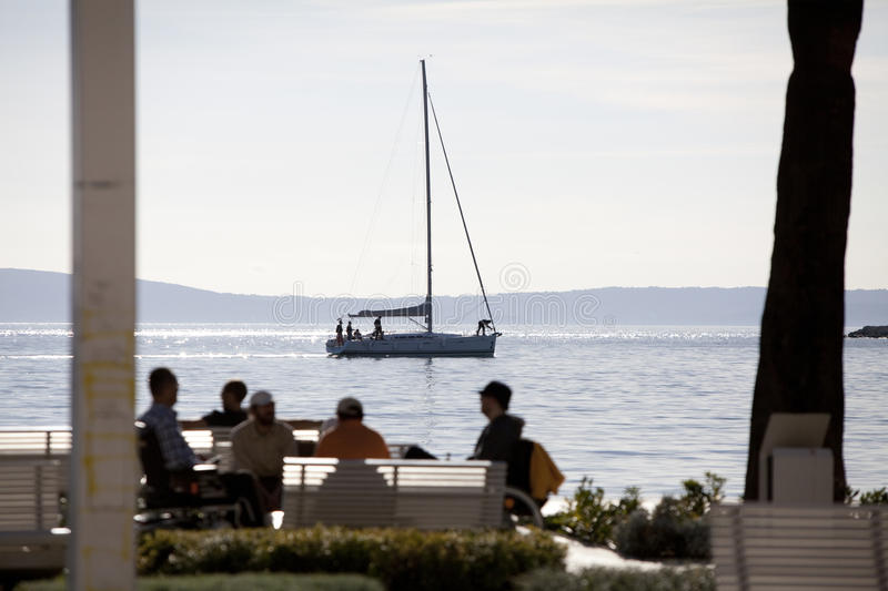 Yacht in the sea town. Sailing yacht moored in the sea town, promenade, people sit on benches stock photo