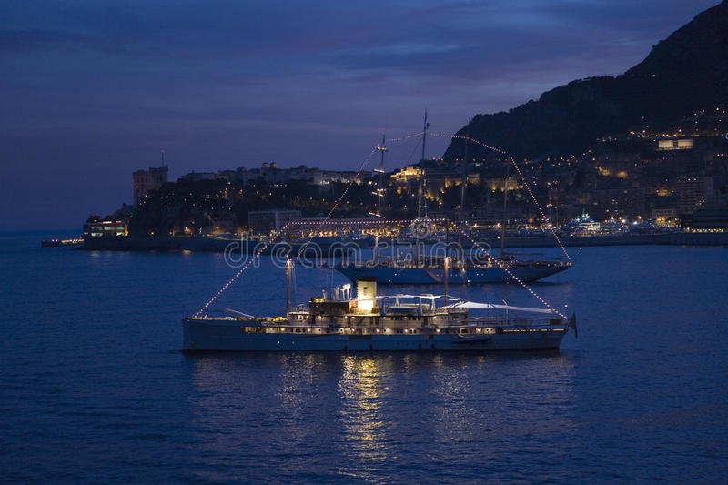 Yacht and seaside night view of Monte-Carlo with lights at dusk, in the Principality of Monaco, Western Europe on the stock photography